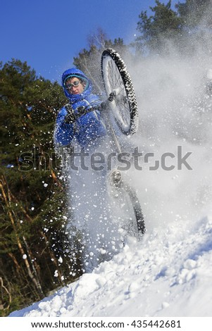 Cyclist riding bike, extreme winter cycling near snowbanks of snowy mountain slope, cross country biking near forest in cool sunny day  - stock photo