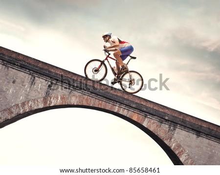 Cyclist riding bike on a bridge - stock photo