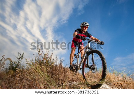 Cyclist riding his bike down on mountain trail. Biker is wearing red sportswear helmet and red glasses. Low point of view. Beautiful sky and clouds on background - stock photo