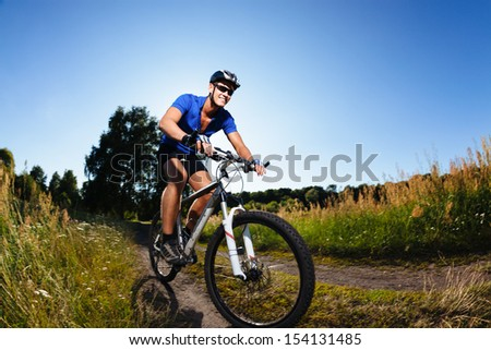 Cyclist riding mountain bike on country road. - stock photo