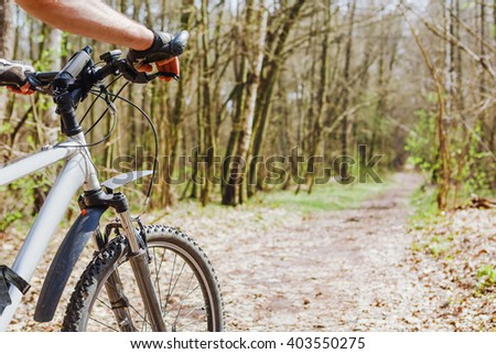 cyclist riding mountain bike on forest trail - stock photo