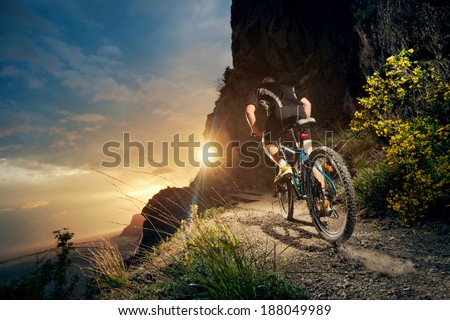 Cyclist riding mountain bike on trail at evening. - stock photo
