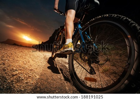 Cyclist riding mountain bike on  trail at sunset. - stock photo