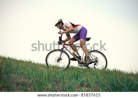 Cyclist riding on a green meadow - stock photo