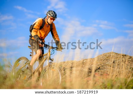 Cyclist Riding the Bike on the Beautiful Autumn Mountain Trail - stock photo