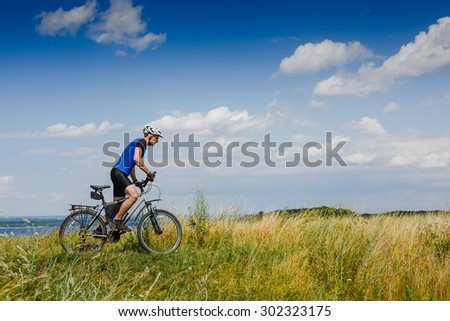 Cyclist Riding the Bike on the Beautiful Spring Meadow Trail