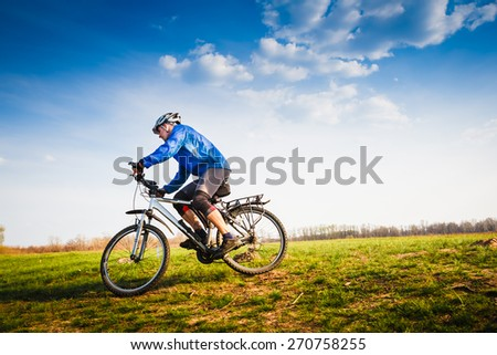 Cyclist Riding the Bike on the Beautiful Spring Trail - stock photo