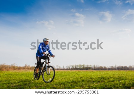 Cyclist Riding the Bike on the Beautiful Summer Meadow trail