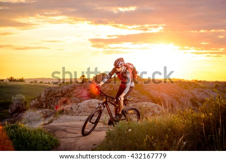 Cyclist Riding the Bike on the Mountain Rocky Trail at Sunset. Extreme Sports - stock photo