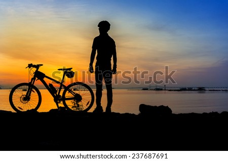 cyclist silhouette at great sunrise - stock photo