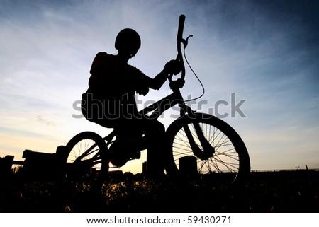 Cyclist silhouette on BMX bike - stock photo