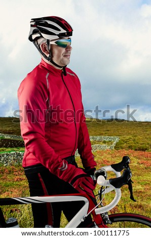 Cyclist standing and loooking to a beautiful green landscape with his bike. - stock photo