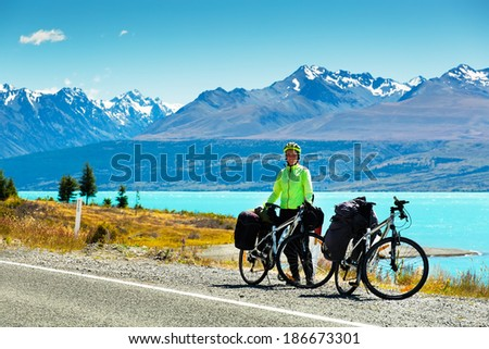 cyclist stands on the winding asphalt mountain road near Lake Pukaki view from Glentanner Park Centre near Mount Cook, on a background of blue sky with clouds, snowy Southern Alps.  - stock photo