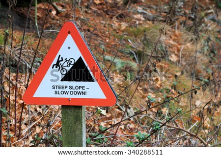 Cyclist steep slope slow down warning sign - stock photo