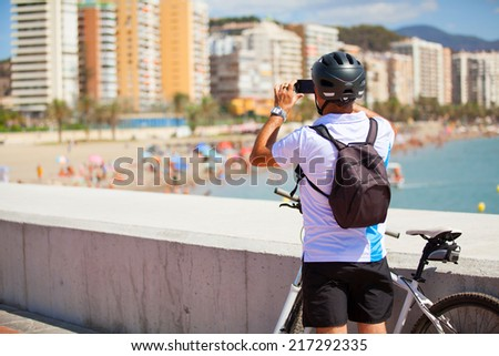 Cyclist taking a photo of the beach - stock photo