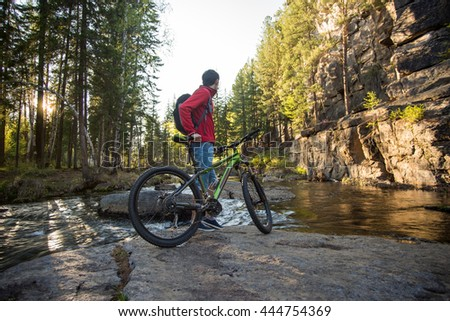 Cyclist with a backpack traveling on a mountain river at sunset - stock photo