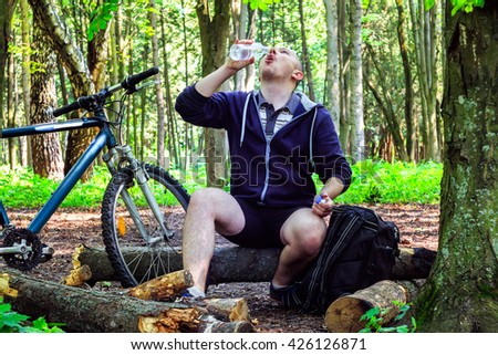 Cyclist with backpack, young man drinking water from bottle, in beautiful forest, summertime journey
