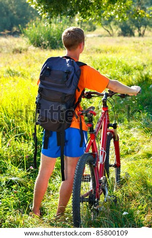 Cyclist with bike and backpack. Position back to us. Summertime travel - stock photo