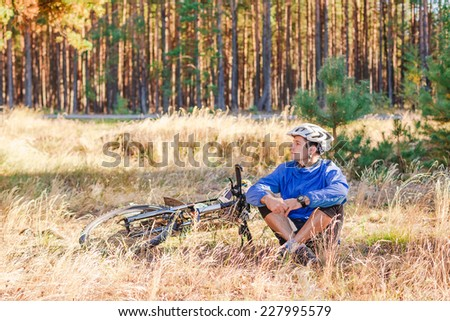 Cyclist with bike have a rest in the forest - stock photo