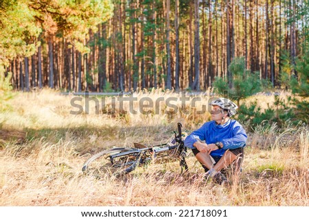 Cyclist with bikehave a rest in autumn forest - stock photo