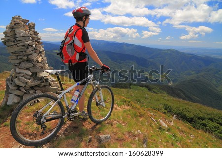 Cyclist with mountain bike stands on top of the mountain - stock photo