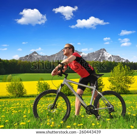 Cyclist with the mountain bike in spring landscape - stock photo