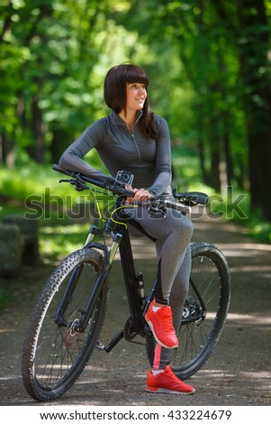 cyclist woman riding a bicycle in park - stock photo
