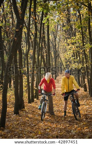 cyclistbiking in autumn forest - stock photo