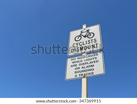 cyclists dismount sign in a bright blue, cloudless sky