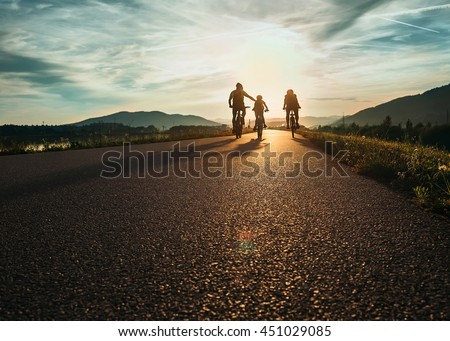 Cyclists family traveling on the road at sunset - stock photo