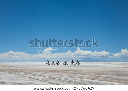 cyclists group riding the desert of salt, in salares de Uyuni, Bolivia. White clouds in the horizon, under a blue sky background - stock photo