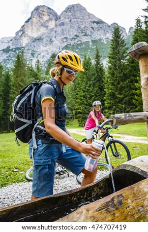 Cyclists on mountain bikes in the Italian dolomites fill the bottle with water.