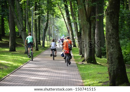 Cyclists ride along  bike path in park - stock photo