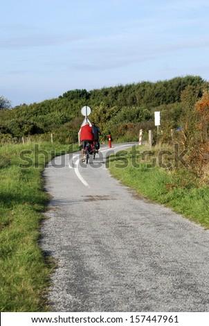 Cyclists riding along cycle path near Vuurtoren sand dunes, Holland - stock photo
