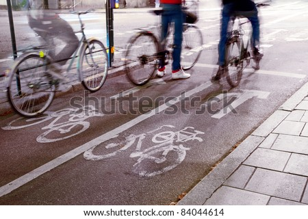Cyclists waiting on their bikes at a crossing - stock photo