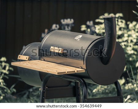 Cylindrical black barbecue with closed cover and smoke pipe in the summer garden of cottage - stock photo