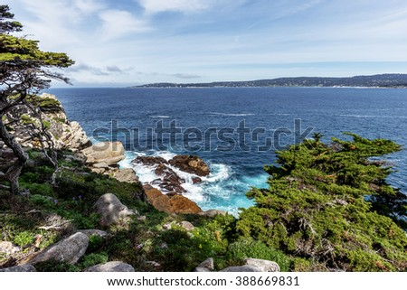 Cypress Cove with its crystal-clear aquamarine waters, surrounded by, unusual geological rock formations and Cypress trees. In the background you Carmel Bay, at point Lobos State Natural Reserve.