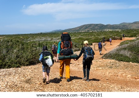 Cyprus. Akamas. Mediterranean Sea. A group of tourists with large backpacks are on the sandy road to the sea - stock photo