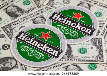 Czech Republic, Brno - January 5,2015: Beermat from Heineken beer and US dollars.Heineken Lager Beer,it was first brewed by Gerard Adriaan Heineken in 1873 - stock photo