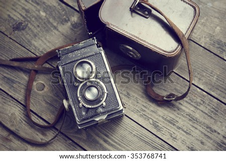 Czech Republic summer 2015 : Old retro camera Rolleiflex and belt bag (leather case) on vintage wooden boards. Illustrative Editorial