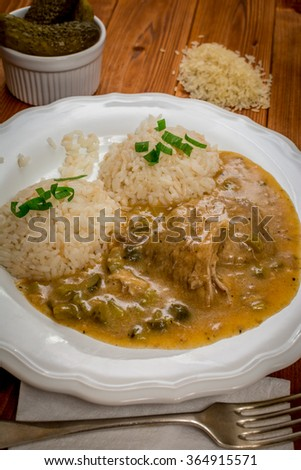 Czech traditional food Znojmo's sauce with gherkin and pork meat and rice on wood table