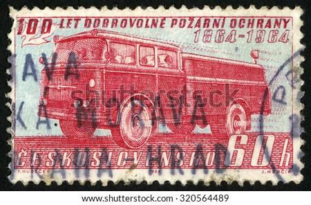 CZECHOSLOVAKIA - CIRCA 1964: post stamp printed in former Czechoslovakia (Ceskoslovensko) shows Skoda fire truck engine; voluntary fire brigades in Bohemia; 100th anniversary; Scott 1250 A477 60h red blue; circa 1964 - stock photo