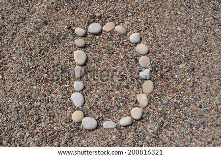 D letter made of stones on sand - stock photo