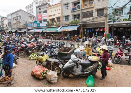 DA LAT, VIETNAM - AUGUST 6, 2016: People buy and sell in shops opposite the Central City Market, Cho Dalat. Dalat is famous with its wine as well as with strawberry and candied fruit.