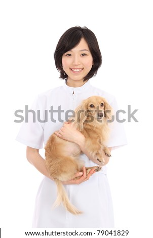 Dachshund and Asian women in white coats - stock photo