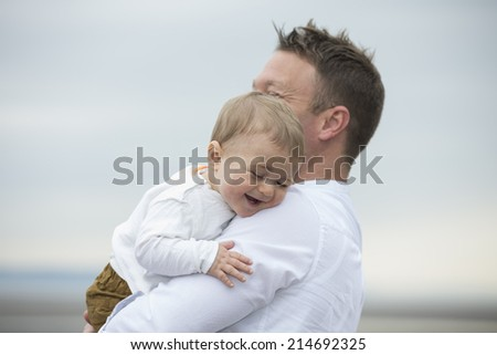 Dad and baby son at the beach. Father and baby boy playing at beach. - stock photo