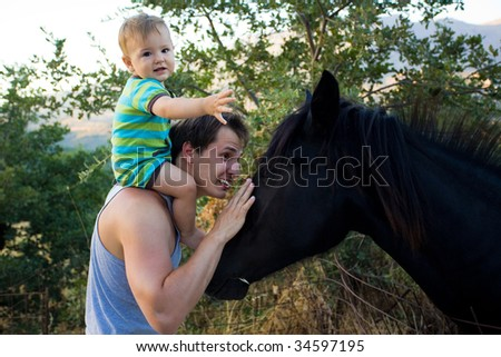 dad and baby son stroking beautiful black horse - stock photo