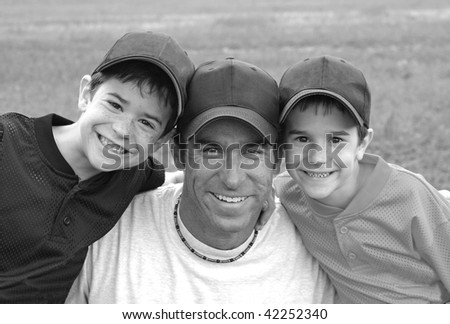 Dad and Boys in their baseball uniforms - stock photo