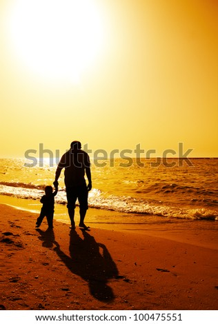 Dad and child on the beach at at sunset - stock photo