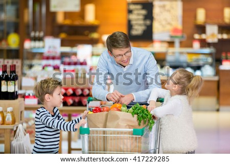 Dad and children with shopping cart - stock photo
